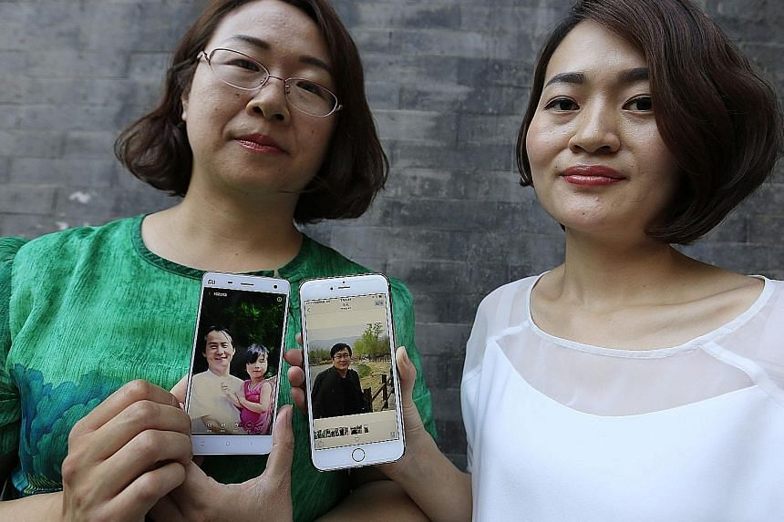 Ms Wang Qiaoling (left) and Ms Li Wenzu with their mobile phones showing photos of their husbands, human rights lawyers Wang Quangzhang and Li Heping, who were arrested last year.