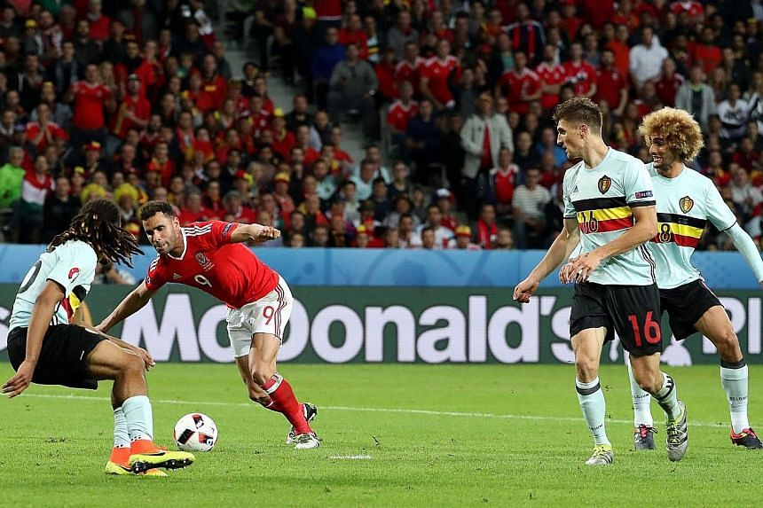 Hal Robson-Kanu (in red), whose contract with English second- tier side Reading has expired, bamboozling the Belgium defence to put Wales 2-1 up, setting them on their way to a memorable last-eight victory.