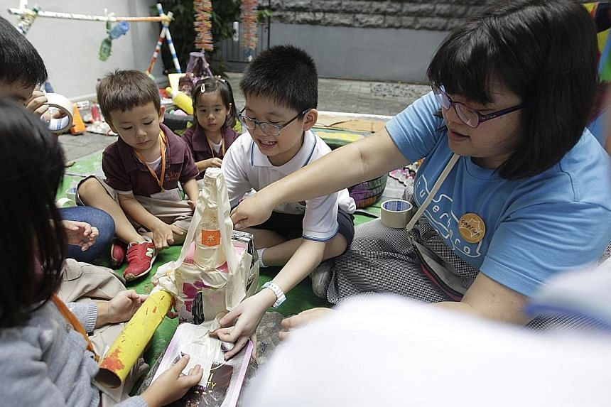 Superhero Me facilitator Chen Weiyan helping kids from Pathlight School (in white) and Odyssey The Global Preschool build a rocket from recycled materials at the Planet of Possibility exhibition.
