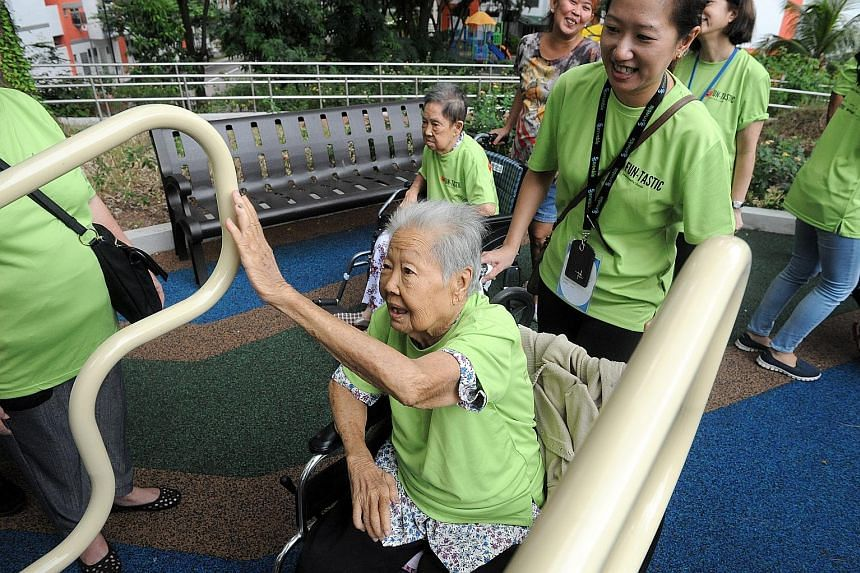 Seniors trying out the exercise equipment at the fitness corner. Republic Poly students and StanChart volunteers were there to help.