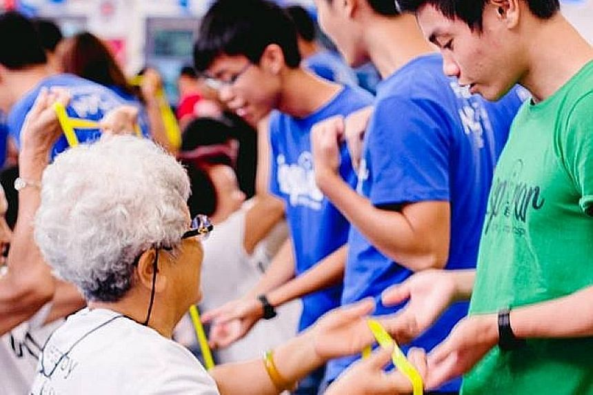 SMU students of Project Inspirar guiding the elderly through the steps of a resistance band exercise at an event held at the Toa Payoh East Community Club. SMU's 2015 graduating class contributed 80 per cent more than the 80 hours of community work t