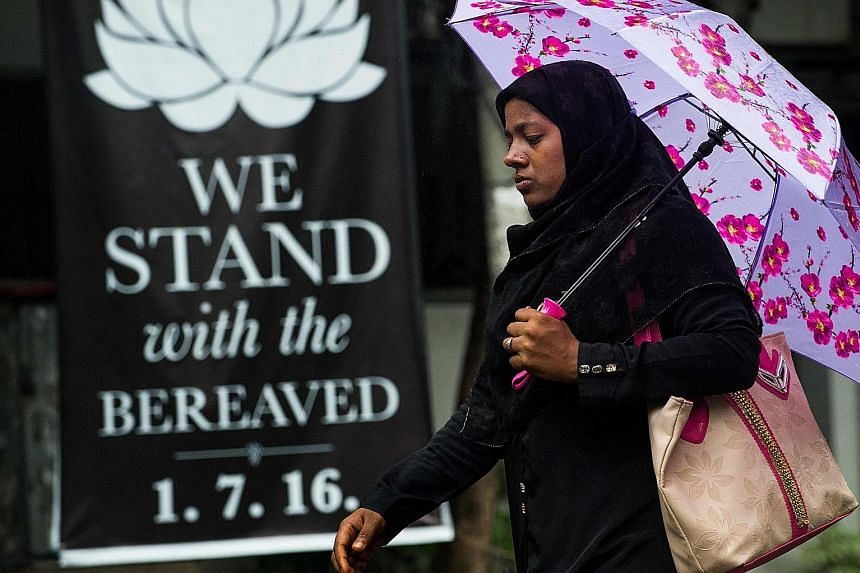 A woman walking past a banner showing support for the loved ones of the victims killed in the bloody cafe siege on July 1. This combination of pictures shows five men - allegedly the gunmen who carried out an attack in Dhaka on July 1, during which 2