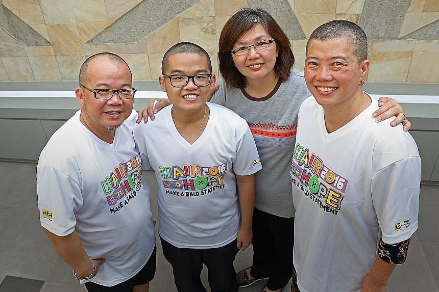 Childhood cancer survivor Jarenn Foo, now 19, with his father Zaric, 51, mother Maria Lim (wearing grey), 49, and Prof Chan (right), who shaved her head in solidarity with the younger Mr Foo.
