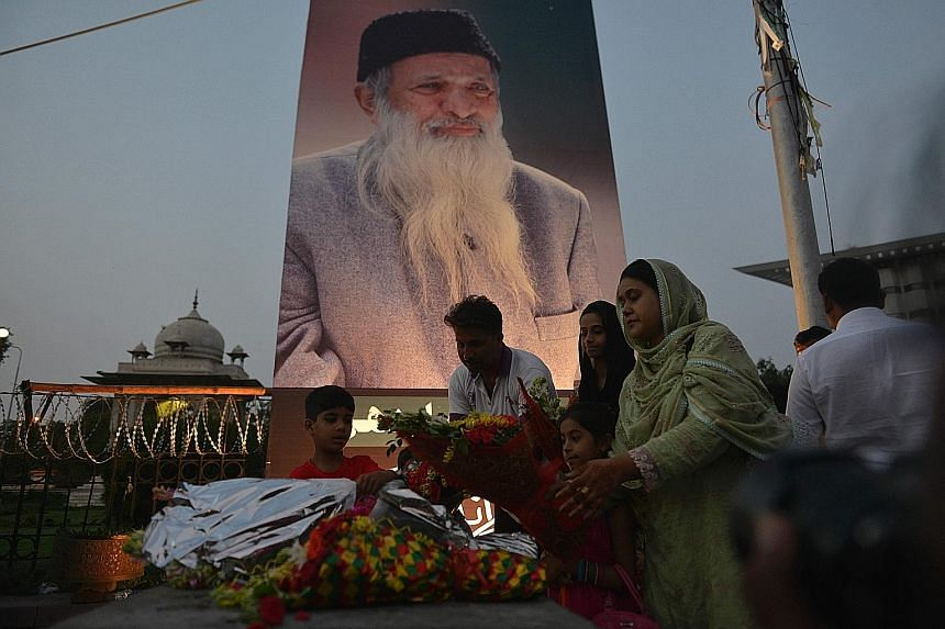 Pakistanis placing flowers before a portrait of Mr Edhi in the capital Islamabad on Saturday. Mr Edhi was revered for setting up maternity wards, morgues, orphanages, shelters and homes for the elderly.