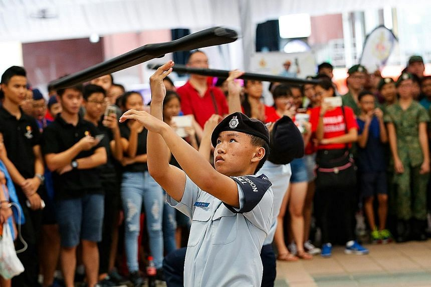 Catholic High School students performing a precision drill with wooden rifle replicas at the Uniformed Groups Carnival yesterday.