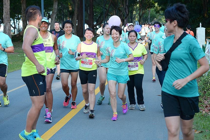 Ms Poo (wearing number 1262), being guided with a hand-held tether by Ms Fu in the Runninghour 2016 race yesterday. Just before this, the Minister for Culture, Community and Youth had run blindfolded for 500m.
