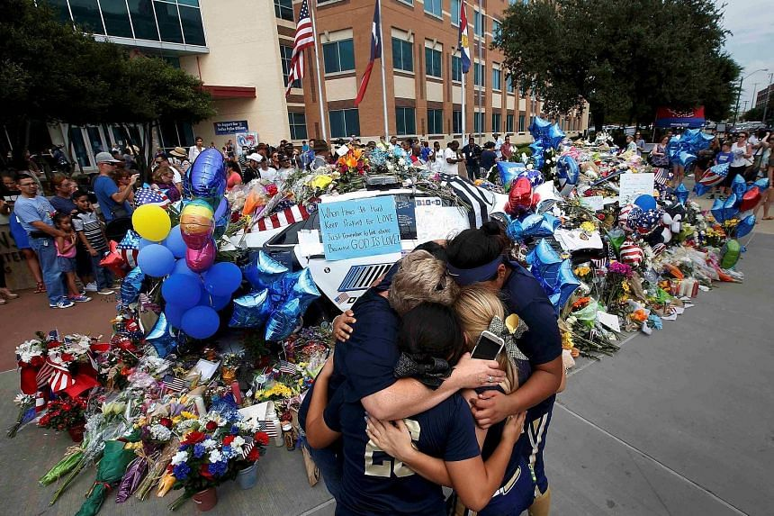 A softball team hugging after paying their respects last Saturday at a makeshift memorial at the Dallas police headquarters following the multiple police shootings in Dallas, Texas.