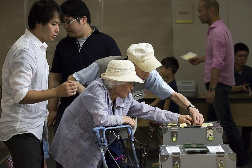 Voters at a polling station in Tokyo yesterday. The huge margin of victory for Japan's ruling LDP-Komeito coalition came despite bubbling unhappiness over Prime Minister Shinzo Abe's flagging Abenomics policy and his professed goal to revise the war-