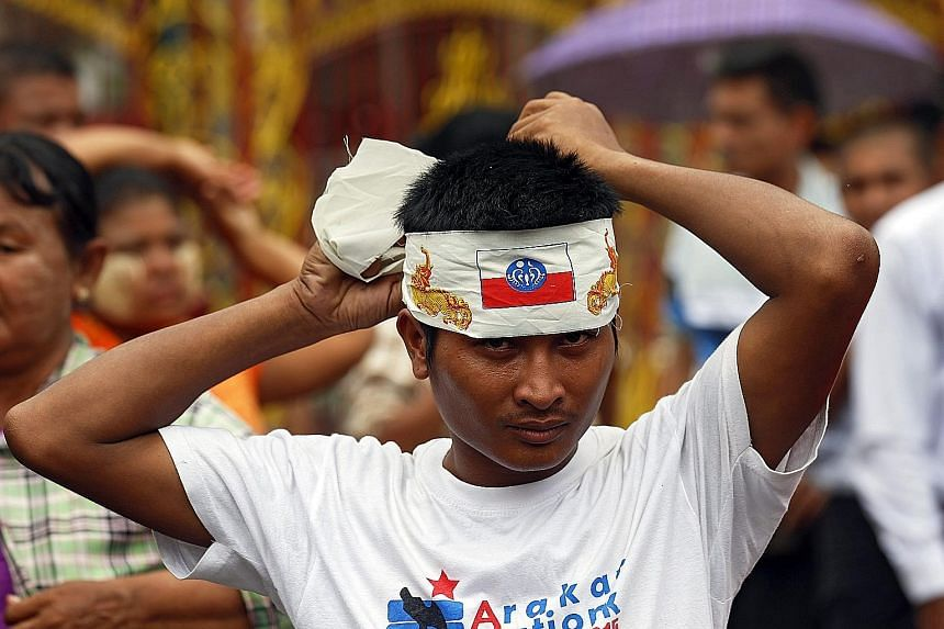 """A protester donning a bandana bearing the Rakhine flag during a Yangon street rally to oppose a government order that the media use the phrase """"Muslims in Rakhine State"""" to refer to the state's population who practise the Islamic faith. The Ministry"""