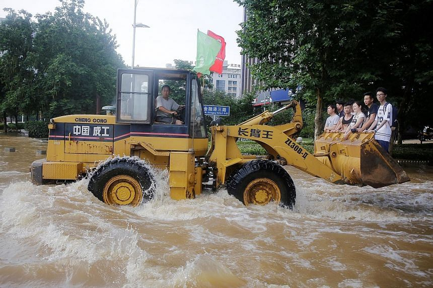 Residents of Wuhan in Hubei province heading to work on an excavator last Friday through churning floodwaters. China has been experiencing widespread flooding as torrential rains batter wide swathes of the country.