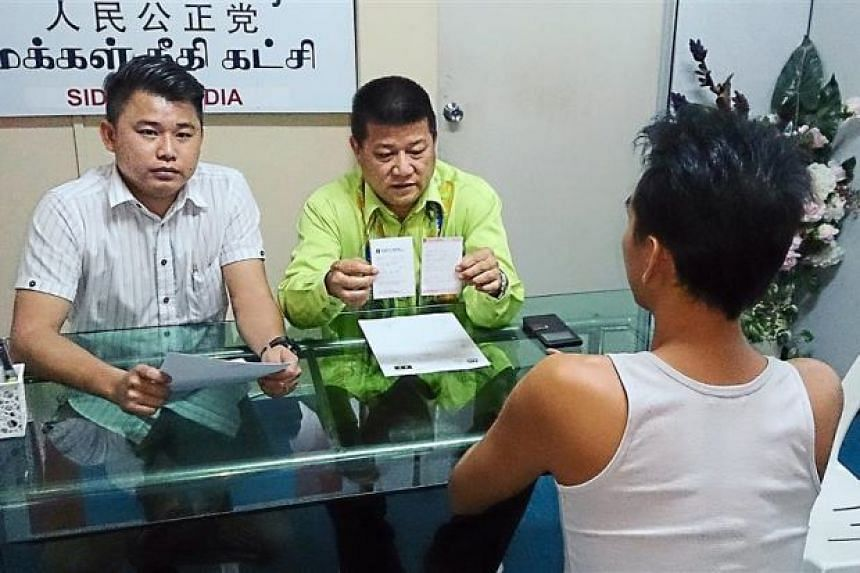 Mr Choo (right) explaning his attempt to become a gigolo to assemblyman Sim Chon Siang (in green).