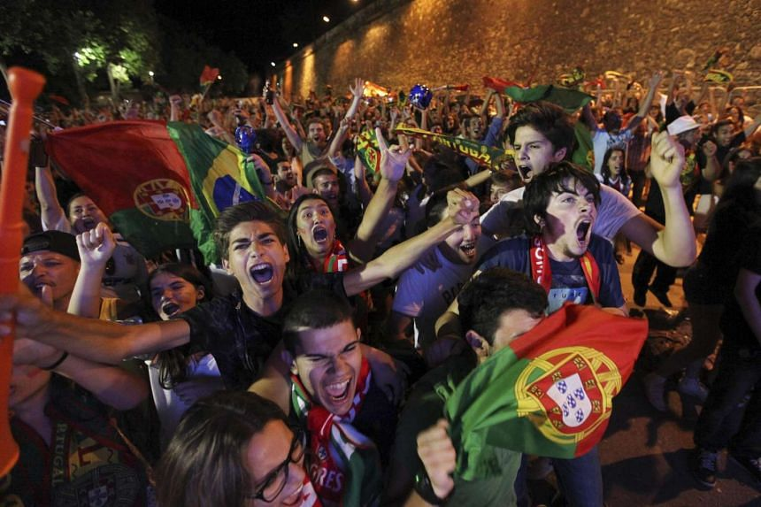 Supporters of Portugal celebrate the victory of their team during the public viewing of the Uefa Euro 2016 final match between Portugal and France at S. Bras Square in Evora, Portugal, July 10.