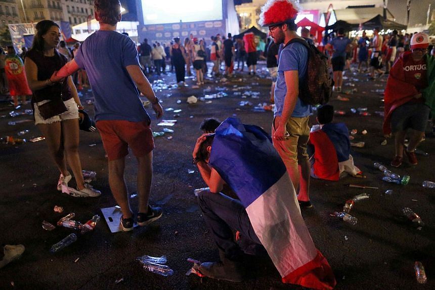 France fans react after their loss to Portugal at the fan zone during the Portugal v France Euro 2016 final soccer match in Lyon, France, July 10.