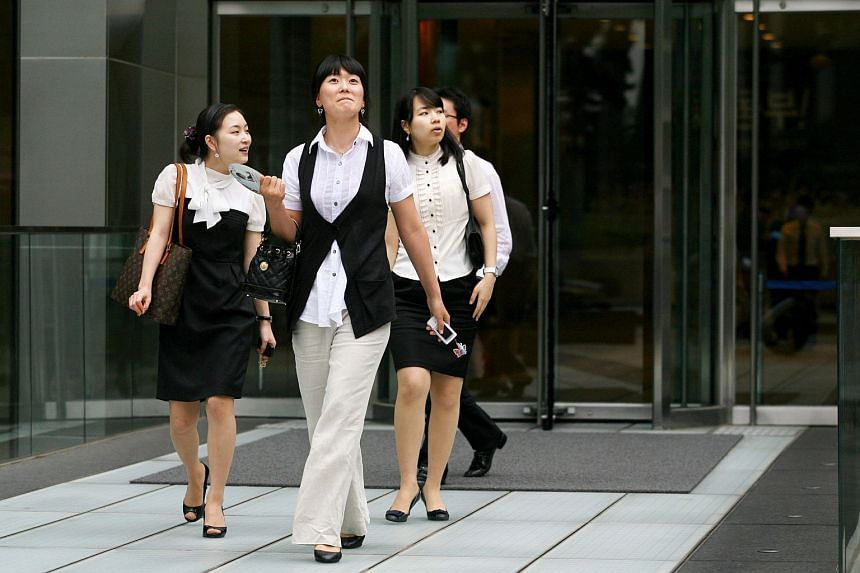 Businesswomen leave an office building in downtown Seoul.