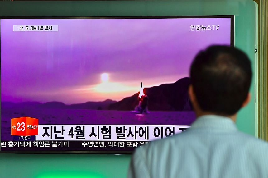 A man watches a television news broadcast at a railway station in Seoul on July 9 showing file footage of a North Korean missile launch.