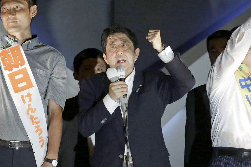 Japan PM Shinzo Abe gestures as he speaks with party candidates during an election campaign rally in Tokyo.