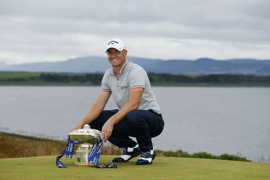 Sweden's Alex Noren celebrates with the trophy after winning the Scottish Open.