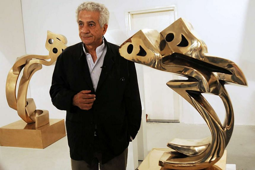 Iranian artist Parviz Tanavoli standing next to his sculptures during an exhibition in the Gulf emirate of Dubai in 2009.