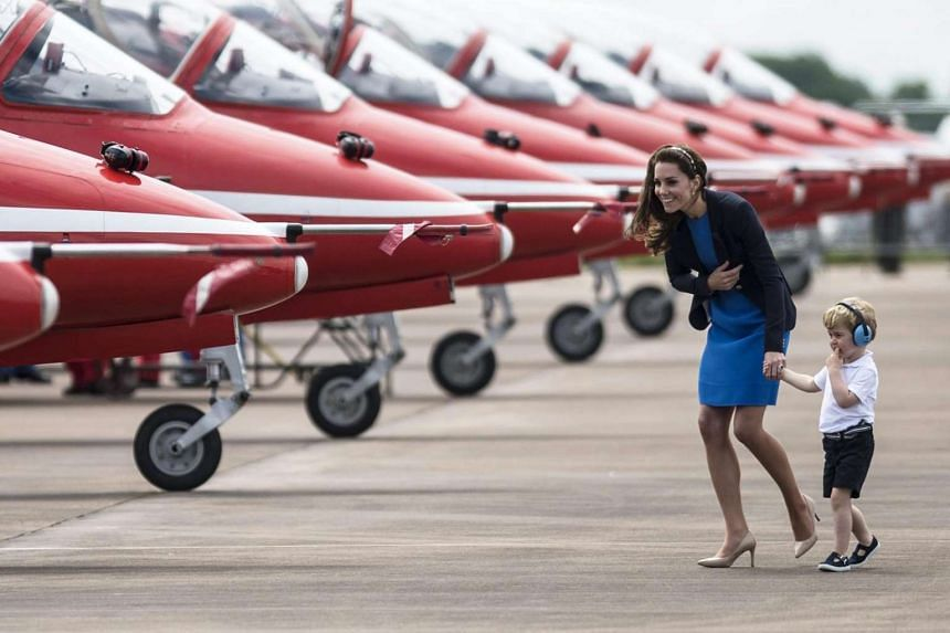 Britain's Catherine Duchess of Cambridge (left) and Prince George (right) walk in front of British Royal Air Force red arrows aerobatic planes during their visit to the Royal Air Force.