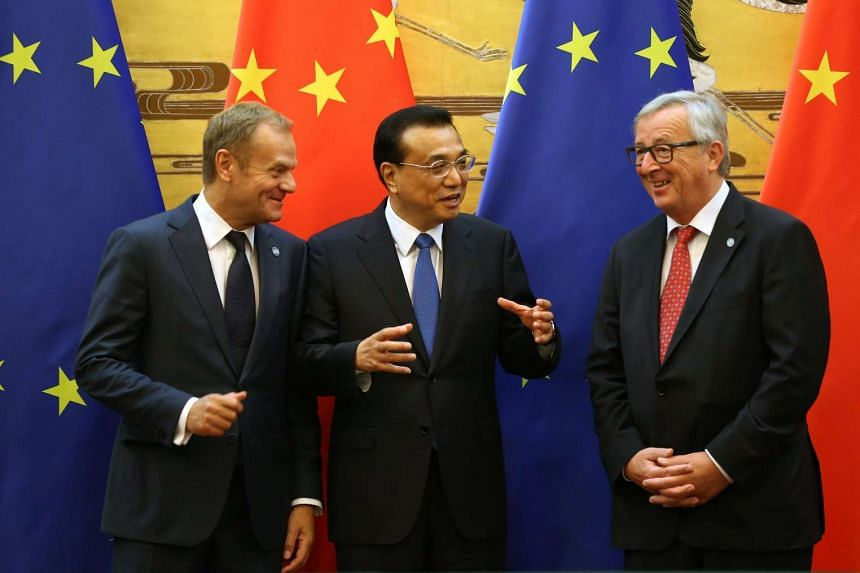 Chinese Premier Li Keqiang (centre) gestures to European Council President Donald Tusk (left) and European Commission President Jean-Claude Juncker at a signing ceremony at the EU-China Summit, on July 12, 2016.