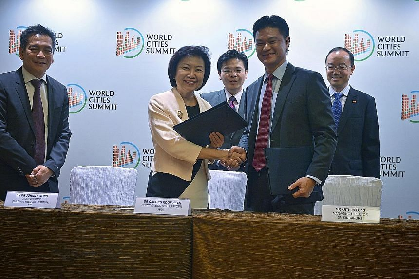 National Development Minister Lawrence Wong (centre) witnessing the sealing of the pact by HDB chief executive Cheong Koon Hean and 3M Singapore managing director Arthur Fong. Beside them are HDB's Building and Research Institute group director Johnn