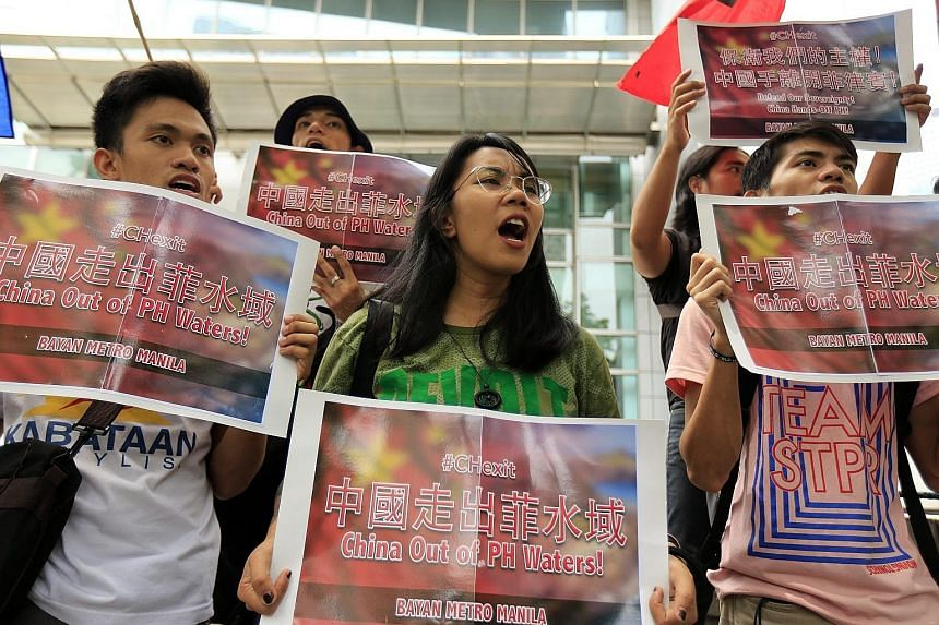 Filipinos staging a demonstration in front of the Chinese consular office in Makati, south of Manila, yesterday. The Permanent Court of Arbitration at The Hague is expected to release its decision today on the case filed by the Philippines challengin