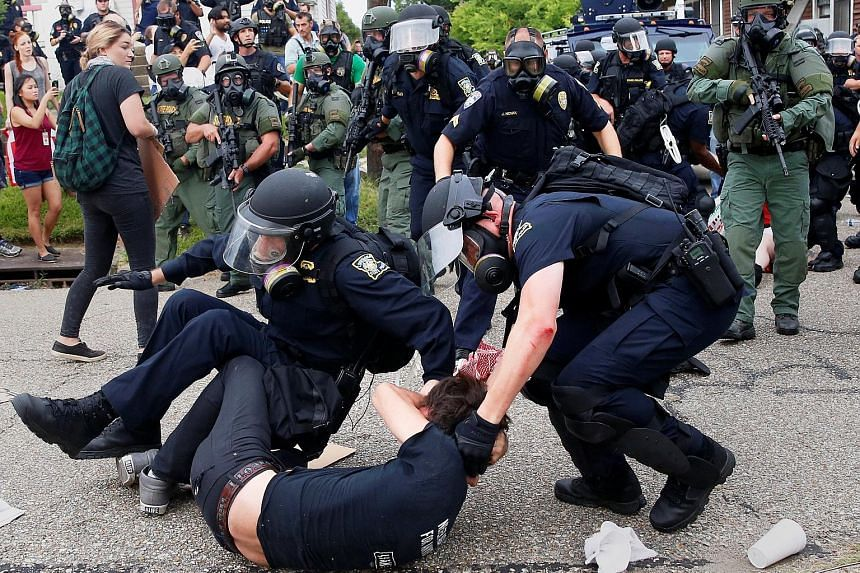 A demonstrator is detained by police officers during protests in Baton Rouge, Louisiana, on Sunday. A similar protest happened in St Paul, Minnesota, around the same time. Both demonstrations were over the police shootings of young black men in those