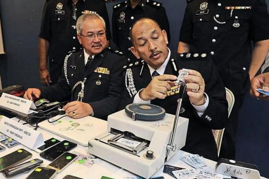 (From left) Penang Commercial Crime Department deputy chief Supt Teh Eng Hin and ACP Mior looking at a cloned credit card during a press conference at the George Town police headquarters.