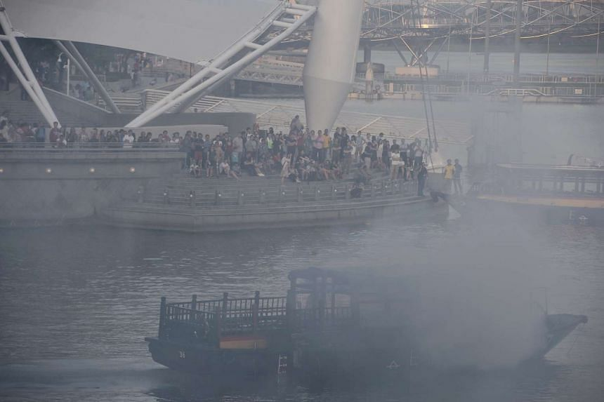 Firemen put out the fire on a boat next to the Esplanade