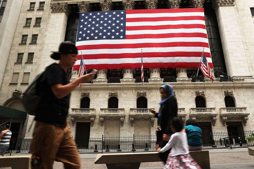 People walk by the New York Stock Exchange (NYSE) on July 5, 2016, in New York City.