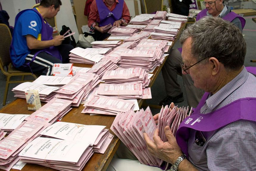 Australian Electoral Commission officials count postal votes for the Australian general election at an official counting centre in central Canberra, on July 6, 2016.