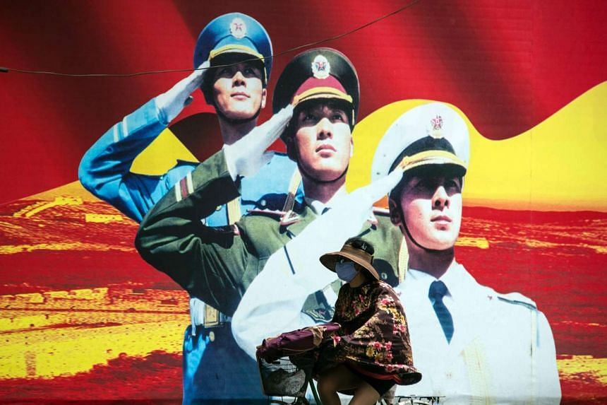 A woman passes a military propaganda poster on a street in Shanghai, on July 12, 2016.