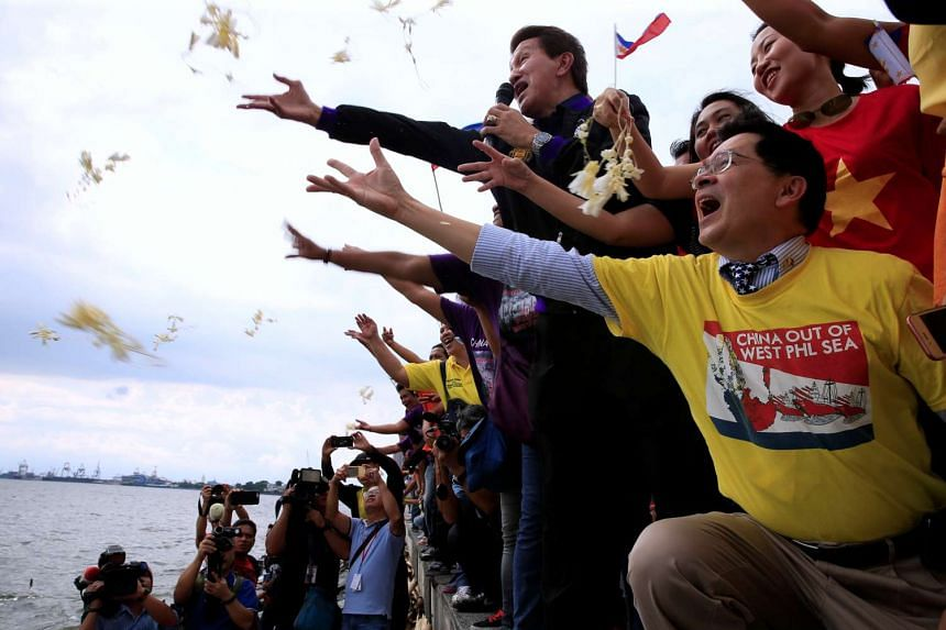 Protesters throw flowers while chanting anti-Chinese slogans at a rally over the South China Sea disputes, along a bay in Manila, on July 12, 2016.