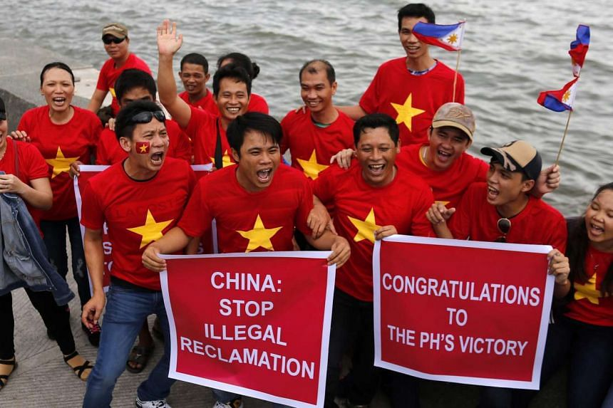 Vietnamese hold placards as they join a demonstration along Roxas Boulevard facing South China sea in Manila, on July 12, 2016.