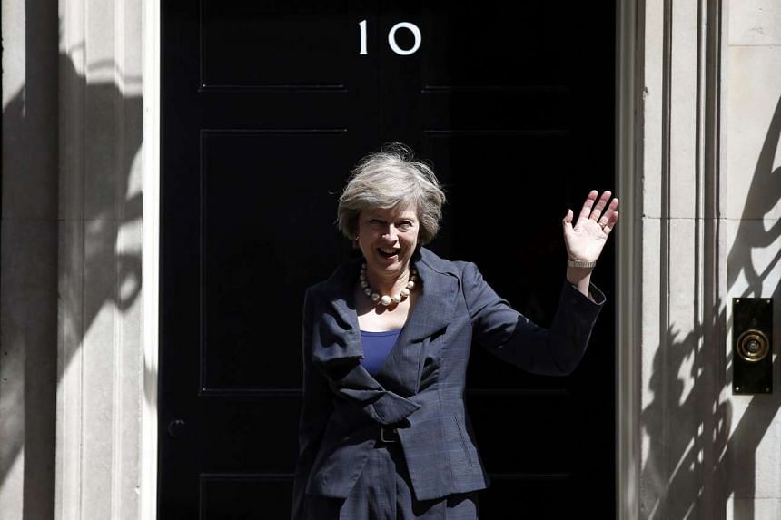 Theresa May waves as she leaves after a cabinet meeting at 10 Downing Street, in central London, on July 12, 2016.