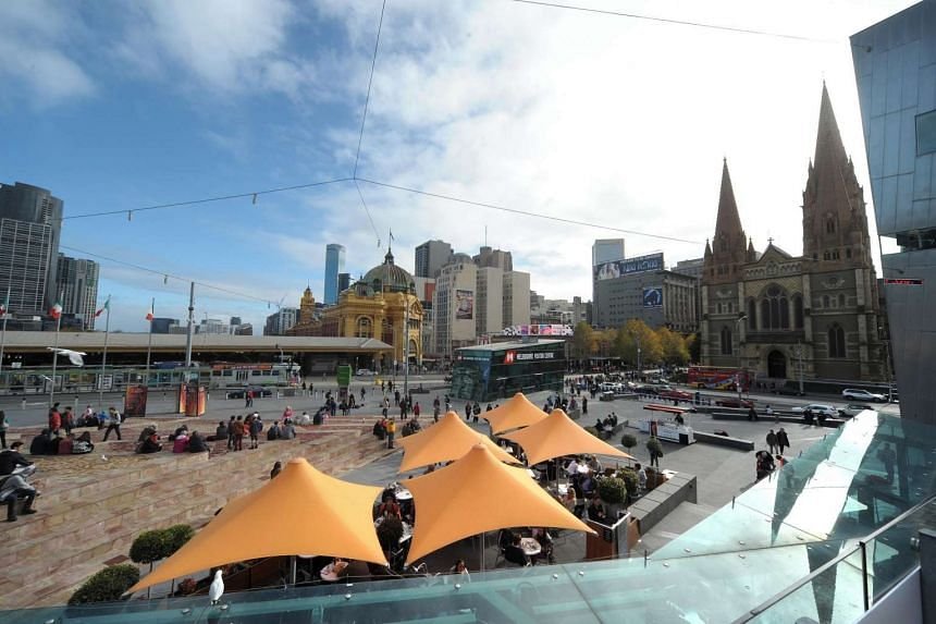 People gather at the entrance to Federation Square in central Melbourne, Australia, in 2013.
