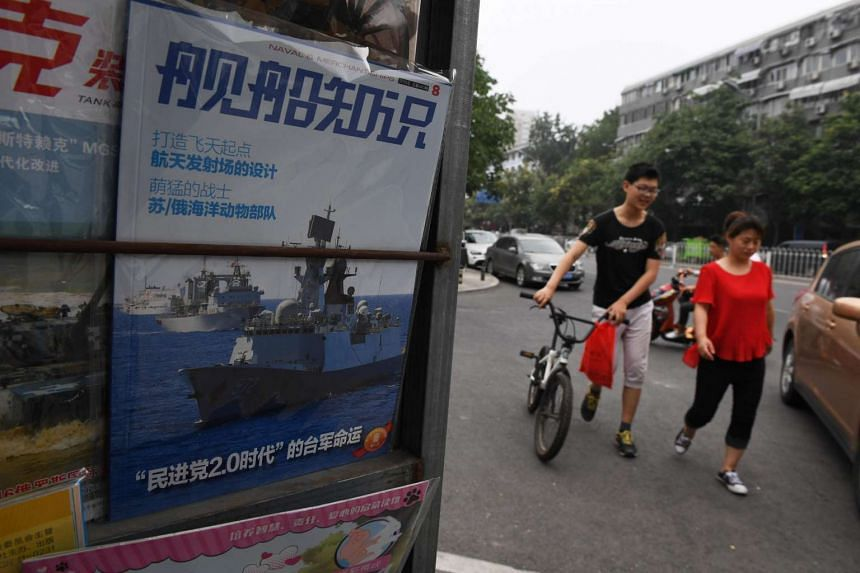 People walk past a military magazine featuring Chinese navy ships, at a news stand in Beijing.