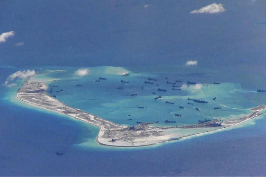 Chinese dredging vessels are purportedly seen in the waters around Mischief Reef in the disputed Spratly Islands in the South China Sea in this still image from video provided by the US Navy in 2015.