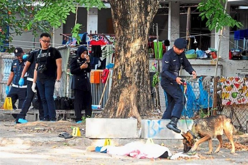 Police officers and the K-9 dog unit inspecting the scene where a Myanmar worker was found dead outside a house.