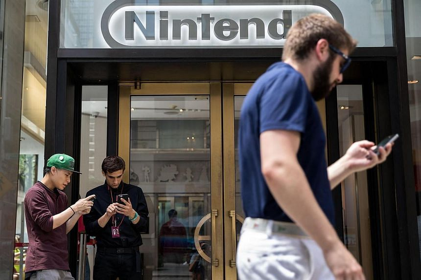 Two men playing Pokemon Go on their smartphones outside Nintendo's flagship store in New York City.