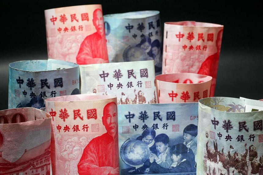 Taiwanese dollar notes are arranged for a photograph in Taipei.
