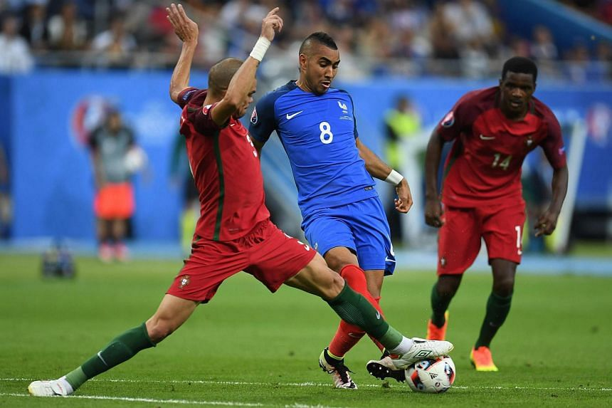 France's forward Dimitri Payet (centre) is challenged for the ball by Portugal's defender Pepe (left) and Portugal's midfielder William Carvalho during the Euro 2016 final football match.