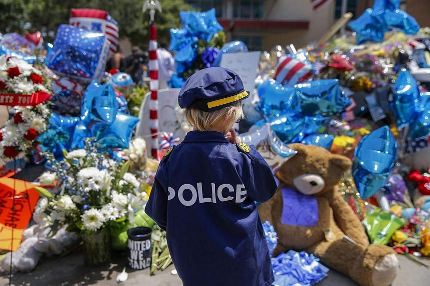 A child dressed in a police uniform costume visits the memorial dedicated to the ones who was killed in the recent shooting incident in Dallas, on July 11.