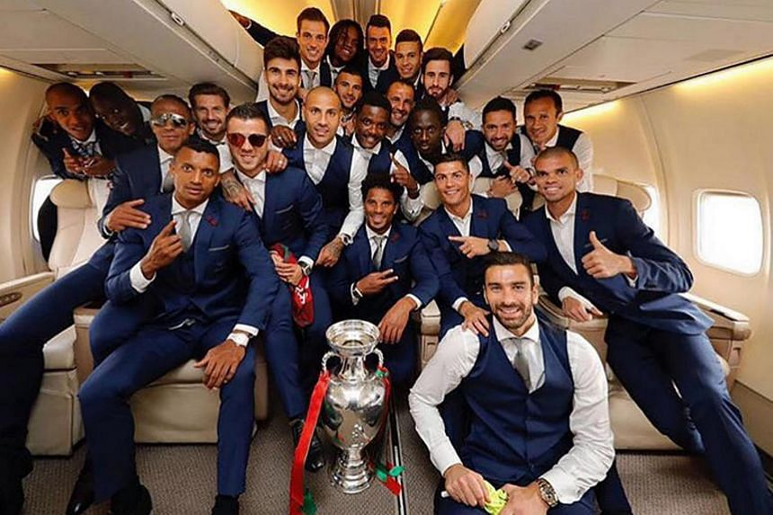 A handout photo released by the Portuguese Football Federation shows Portugal's national football team players posing with the trophy aboard the plane returning to Portugal on July 11.