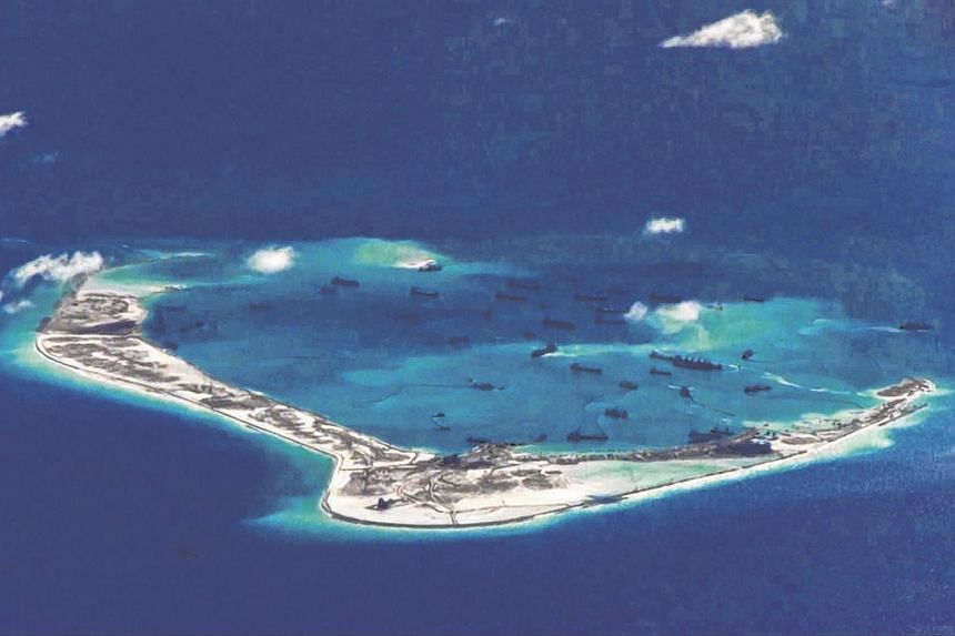 Chinese dredging vessels are purportedly seen in the waters around Mischief Reef in the disputed Spratly Islands in the South China Sea in this still image from a video provided by the US Navy in 2015.
