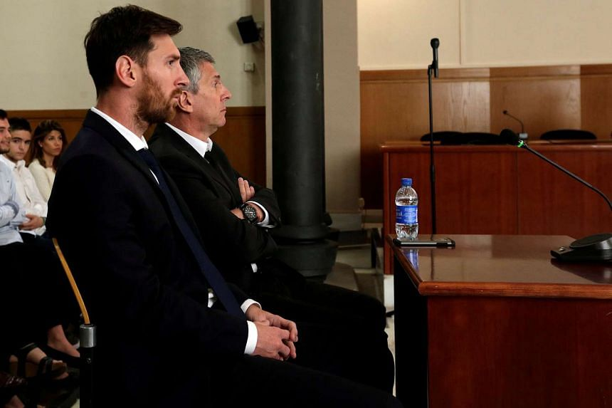 Barcelona's Argentine football player Lionel Messi sits in court with his father Jorge Horacio Messi during their trial for tax fraud in Barcelona, Spain.