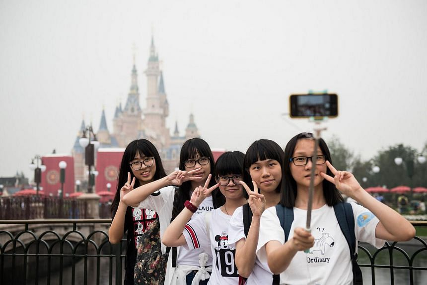 Visitors take a selfie after the opening ceremony of the Shanghai Disney Resort in Shanghai on June 16.