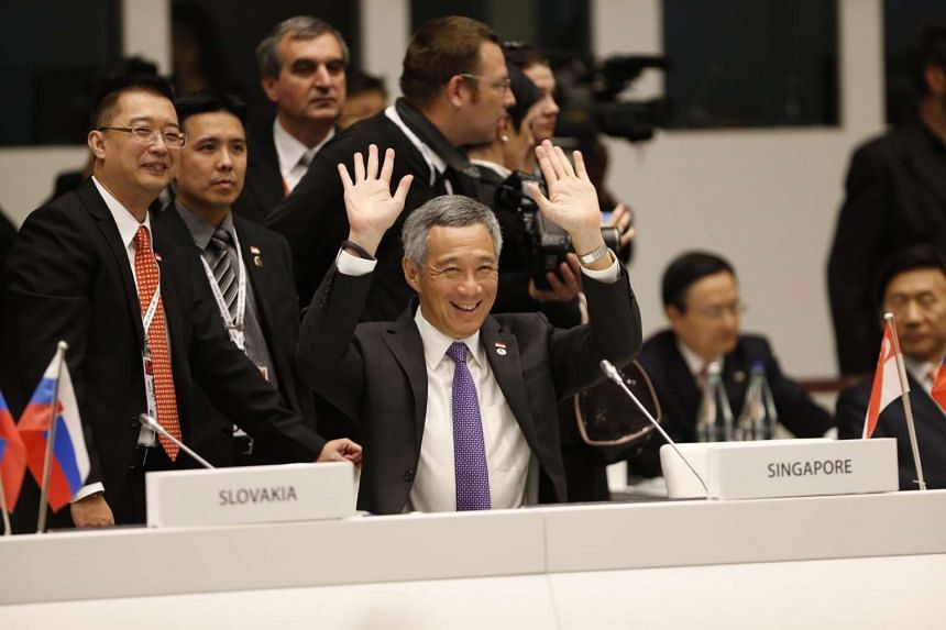 PM Lee Hsien Loong waving to fellow Asian and European leaders at the opening ceremony of the 10th Asia-Europe Meeting (Asem) in Milan, Italy, on Oct 16, 2014.