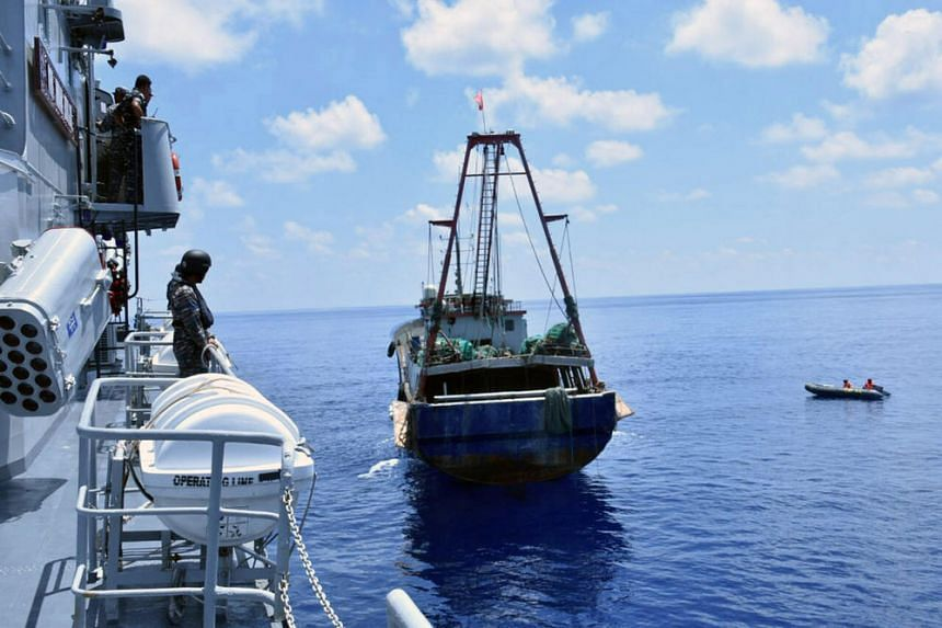 The Indonesian Navy vessel KRI Imam Bonjol (left) inspects the Chinese flagged fishing boat Han Tan Cou near Natuna Islands on June 17, 2016.