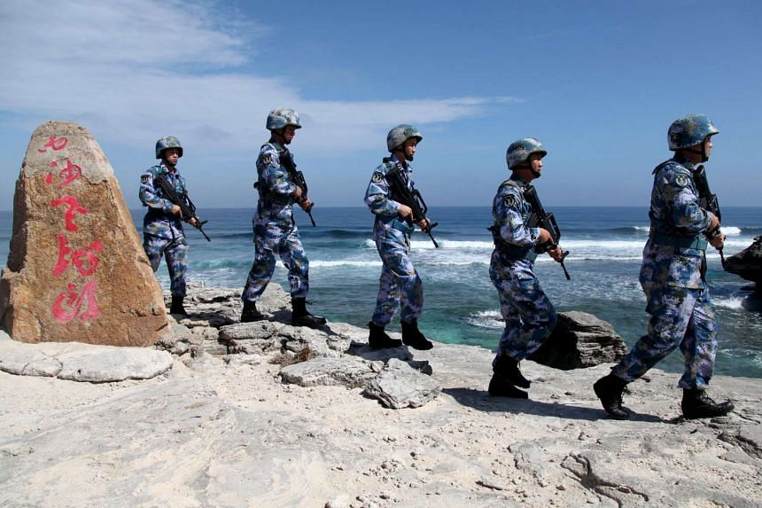 Soldiers of China's People's Liberation Army (PLA) Navy patrol at Woody Island in the South China Sea.